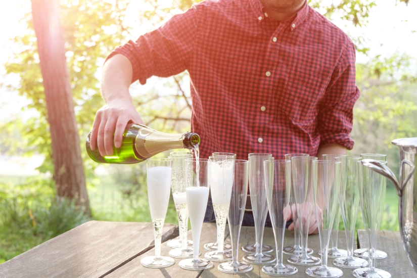 man pouring champagne in flutes glasses